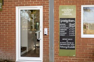 Welcome back to the Larder - Cafe front door and opening hours sign